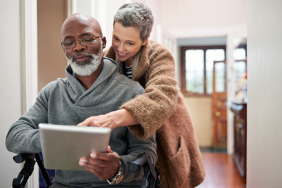 An African American couple review documents on an electronic tablet